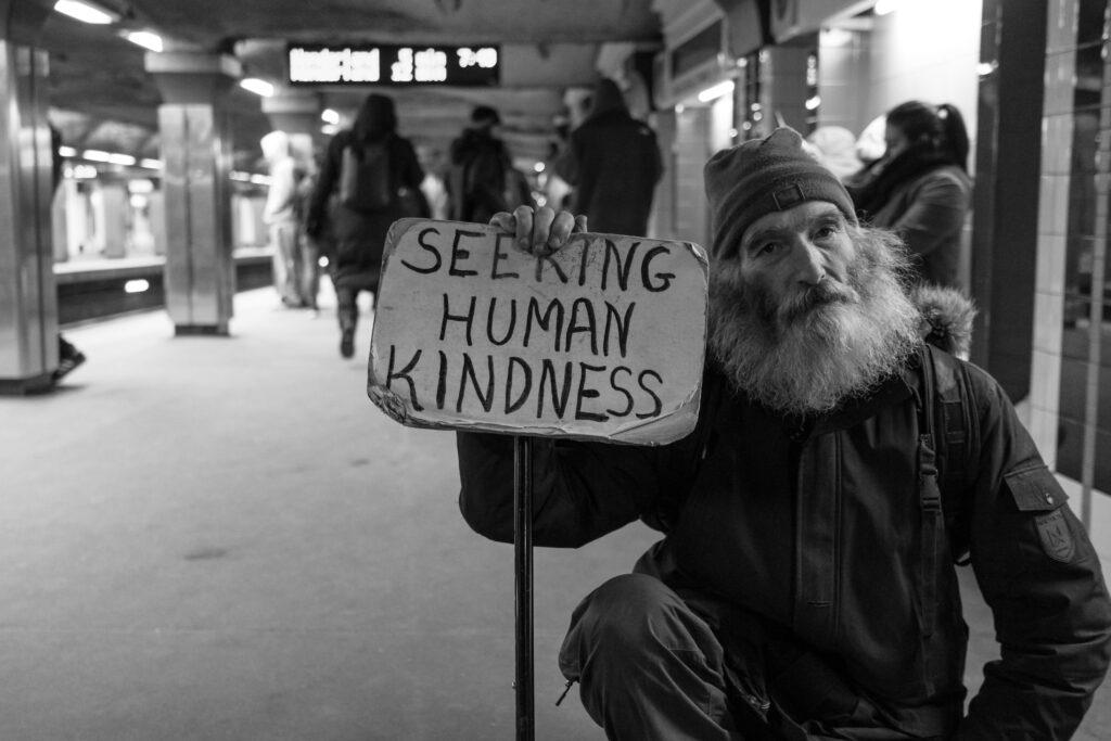 elderly man holding sign that reads seeking human kindness, photo by Matt Collamer via upsplash.com