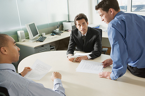 image of three men sitting around a office desk