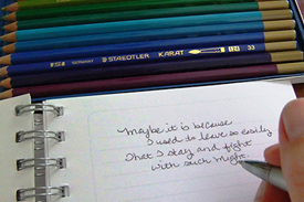 image of a pencils and a person writing