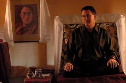Stephen sitting on a cushion in a robe