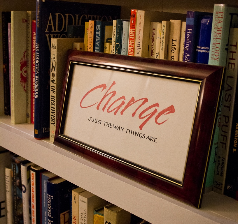 image of a sign that says 'Change is just the way things are' on a bookshelf